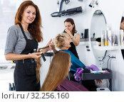 Купить «Hairdresser doing styling of girl», фото № 32256160, снято 26 июня 2018 г. (c) Яков Филимонов / Фотобанк Лори