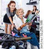 Купить «Young woman hairdresser in hair salon helping to senior woman choosing hairstyling», фото № 32256188, снято 26 июня 2018 г. (c) Яков Филимонов / Фотобанк Лори