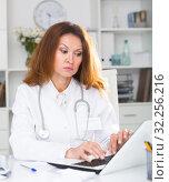Купить «Young therapist woman in uniform is working behind laptop with documents», фото № 32256216, снято 30 мая 2018 г. (c) Яков Филимонов / Фотобанк Лори