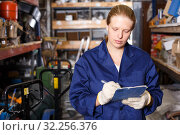 Young female worker holding notebook and looking construction materials at shelves. Стоковое фото, фотограф Яков Филимонов / Фотобанк Лори