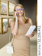 Купить «Woman visiting gallery and talking on phone», фото № 32256412, снято 22 сентября 2018 г. (c) Яков Филимонов / Фотобанк Лори