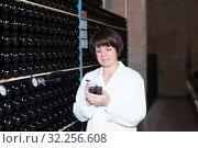 Купить «Female observing fermentation of wine», фото № 32256608, снято 10 ноября 2016 г. (c) Яков Филимонов / Фотобанк Лори