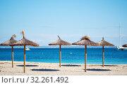 Idyllic scenery, concept of summer holidays, straw parasols in a row on the coast of blue Mediterranean Sea, Majorca Island, Baleares, Spain (2018 год). Стоковое фото, фотограф Alexander Tihonovs / Фотобанк Лори