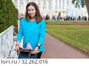 Купить «Portrait of satisfied adult woman closing her leather bag, looking at camera, standing in urban park, copyspace», фото № 32262016, снято 24 августа 2019 г. (c) Кекяляйнен Андрей / Фотобанк Лори