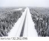 Aerial view at wintry road during snowy storm, highway in northern forest. Стоковое фото, фотограф Кекяляйнен Андрей / Фотобанк Лори