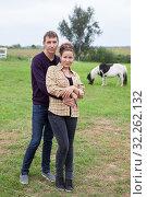 Купить «Young couple embracing in farmland, portrait of young man nand woman in countryside, horse is on background», фото № 32262132, снято 23 июля 2016 г. (c) Кекяляйнен Андрей / Фотобанк Лори