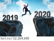 Купить «Businessman jumping from year 2019 to 2020», фото № 32264640, снято 21 января 2020 г. (c) Elnur / Фотобанк Лори