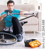 Купить «Young man repairing bicycle at home», фото № 32264688, снято 7 марта 2018 г. (c) Elnur / Фотобанк Лори