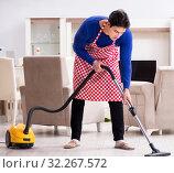 Купить «Young man vacuum cleaning his apartment», фото № 32267572, снято 13 марта 2018 г. (c) Elnur / Фотобанк Лори