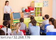 Купить «Teacher standing at blackboard in classroom», фото № 32268176, снято 28 января 2018 г. (c) Яков Филимонов / Фотобанк Лори