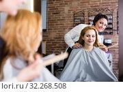 Купить «Adult hairdresser is listening to wishes of young woman», фото № 32268508, снято 7 марта 2017 г. (c) Яков Филимонов / Фотобанк Лори