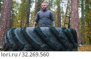 Купить «A big man bodybuilder standing near the tire.», фото № 32269560, снято 16 октября 2019 г. (c) Константин Шишкин / Фотобанк Лори