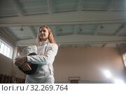 Купить «A portrait of a young woman fencer holding her helmet», фото № 32269764, снято 5 октября 2019 г. (c) Константин Шишкин / Фотобанк Лори
