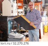Купить «Mature man carefully examining antiques», фото № 32270276, снято 15 мая 2018 г. (c) Яков Филимонов / Фотобанк Лори