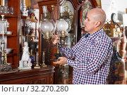Купить «Serious male carefully examining antiques», фото № 32270280, снято 15 мая 2018 г. (c) Яков Филимонов / Фотобанк Лори