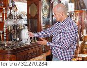Купить «Adult male carefully examining antiques», фото № 32270284, снято 15 мая 2018 г. (c) Яков Филимонов / Фотобанк Лори