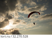Sochi/Russia - August 4,2019: Two people in a paraglider tandem fly in the sky. Редакционное фото, фотограф Женя Канашкин / Фотобанк Лори