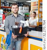 Купить «Guy customer showing instruments in store, woman seller working», фото № 32270764, снято 17 мая 2018 г. (c) Яков Филимонов / Фотобанк Лори