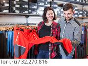 Купить «Cheerful couple examining touristic trousers», фото № 32270816, снято 8 марта 2017 г. (c) Яков Филимонов / Фотобанк Лори