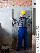 Купить «Professional constructor in helmet is measuring wall», фото № 32270924, снято 3 июня 2017 г. (c) Яков Филимонов / Фотобанк Лори