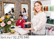 Купить «Portrait of young woman administrator inviting to beauty salon», фото № 32270940, снято 25 апреля 2018 г. (c) Яков Филимонов / Фотобанк Лори