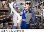 Купить «worker choosing flexible aluminum pipe for ventilation in workshop», фото № 32270980, снято 15 марта 2017 г. (c) Яков Филимонов / Фотобанк Лори
