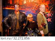 England, London, Marylebone, Interior View of Madam Tussauds, Tourist Posing with Waxwork Figures of Arnold Schwarzenegger and Bruce Willis. Стоковое фото, фотограф Steve Vidler / age Fotostock / Фотобанк Лори