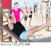 Купить «Sporty women and men during training outdoors on sunny beach», фото № 32275948, снято 14 июня 2017 г. (c) Яков Филимонов / Фотобанк Лори