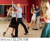 Купить «Positive adult couples dancing tango together in modern studio», фото № 32276108, снято 4 октября 2018 г. (c) Яков Филимонов / Фотобанк Лори
