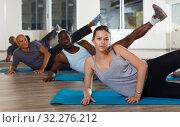 Купить «Adult women and men exercising during yoga class», фото № 32276212, снято 30 июля 2018 г. (c) Яков Филимонов / Фотобанк Лори