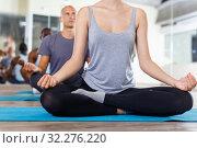 Купить «Closeup of slim body of young woman meditating in yoga position Padmasana during group training in studio», фото № 32276220, снято 30 июля 2018 г. (c) Яков Филимонов / Фотобанк Лори