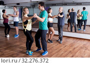 Купить «Group of smiling people dancing bachata together», фото № 32276372, снято 22 октября 2019 г. (c) Яков Филимонов / Фотобанк Лори