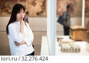 Купить «Young chinese woman visitor looking to art objects under glass», фото № 32276424, снято 24 февраля 2020 г. (c) Яков Филимонов / Фотобанк Лори