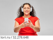 Купить «woman in headphones listens to music on smartphone», фото № 32278648, снято 15 сентября 2019 г. (c) Syda Productions / Фотобанк Лори