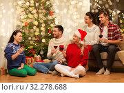 Купить «friends celebrating christmas and drinking wine», фото № 32278688, снято 17 декабря 2017 г. (c) Syda Productions / Фотобанк Лори