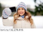 Купить «woman taking selfie by smartphone in winter», фото № 32278816, снято 20 января 2019 г. (c) Syda Productions / Фотобанк Лори