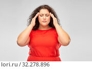 woman in red dress suffering from headache. Стоковое фото, фотограф Syda Productions / Фотобанк Лори