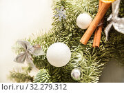 Купить «Fragment of a Christmas wreath of fir branches decorated with balls, cinnamon stick, bows and snowflakes», фото № 32279312, снято 1 января 2019 г. (c) Юлия Бабкина / Фотобанк Лори