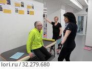 Купить «Инструктор рассказывает, как правильно выполнять упражнение», эксклюзивное фото № 32279680, снято 7 февраля 2018 г. (c) ДеН / Фотобанк Лори