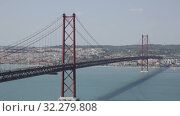 Купить «Panoramic view of 25 de Abril Bridge - suspension bridge across Tagus river connecting Lisbon city to municipality of Almada, Portugal», видеоролик № 32279808, снято 13 мая 2019 г. (c) Яков Филимонов / Фотобанк Лори
