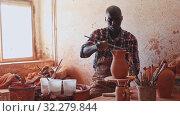Купить «Professional African American male potter painting ceramic pot in pottery workshop», видеоролик № 32279844, снято 23 октября 2019 г. (c) Яков Филимонов / Фотобанк Лори