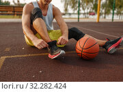 Купить «Basketball player tying laces on outdoor court», фото № 32282424, снято 13 июня 2019 г. (c) Tryapitsyn Sergiy / Фотобанк Лори