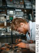 Купить «Strange scientist works with soldering iron in lab», фото № 32282432, снято 17 июня 2019 г. (c) Tryapitsyn Sergiy / Фотобанк Лори