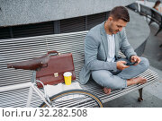 Businessman with bike resting on bench in downtown. Стоковое фото, фотограф Tryapitsyn Sergiy / Фотобанк Лори