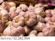Купить «heads of fragrant garlic in baskets on market counter», фото № 32282904, снято 26 мая 2018 г. (c) Татьяна Яцевич / Фотобанк Лори
