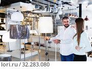 Купить «family touching floor lamp in the furniture store», фото № 32283080, снято 29 января 2018 г. (c) Яков Филимонов / Фотобанк Лори