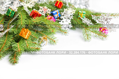 Купить «Christmas or New Year tree branches decorated with small gift boxes of different colors and snowflakes, on white background», фото № 32284176, снято 10 октября 2019 г. (c) Юлия Бабкина / Фотобанк Лори