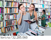 Купить «boy talking on mobile phone while buying books with friend in store», фото № 32285060, снято 16 сентября 2016 г. (c) Яков Филимонов / Фотобанк Лори