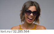 Купить «happy laughing young woman in black sunglasses», видеоролик № 32285564, снято 7 октября 2019 г. (c) Syda Productions / Фотобанк Лори