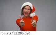 Купить «woman in santa hat showing thumbs up on christmas», видеоролик № 32285620, снято 7 октября 2019 г. (c) Syda Productions / Фотобанк Лори